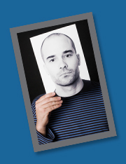 Man holding up a photo of another man's face in front of his own face