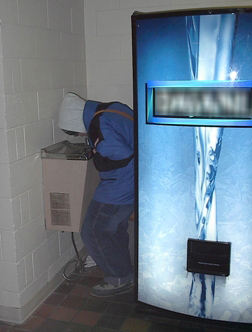 Young man sqeezing past a water bottle machine to access a cramped water fountain