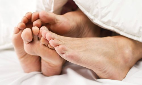 The bare feet of a couple who are in bed together