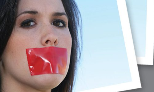 Woman with mouth covered by red tape