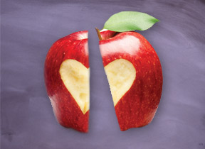 An apple with a heart share carved into it, sliced in two