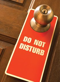 "A ""Do Not Disturb"" notice hanging from a door knob"